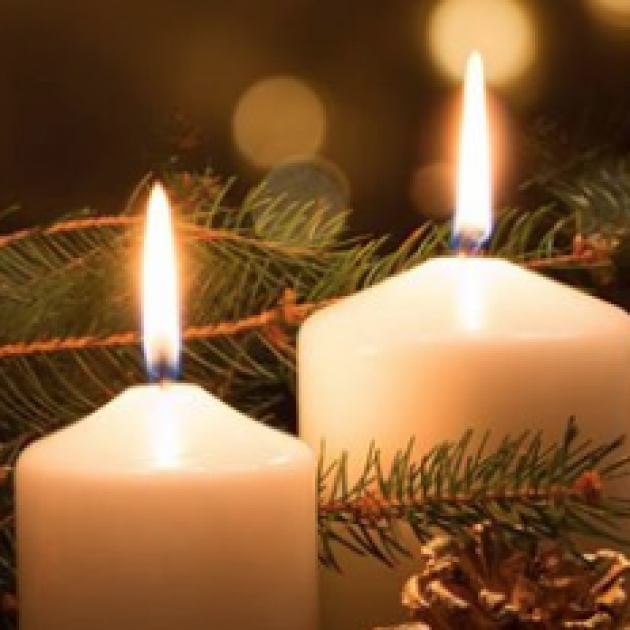 Two candles with close up on flames and pine branches in background