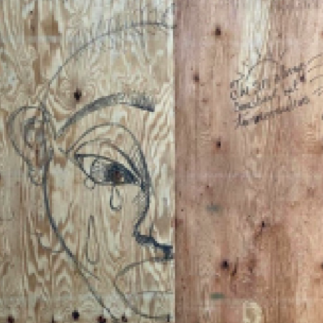 Face drawn crying on a piece of wood