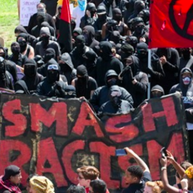 People outside with Smash Racism sign