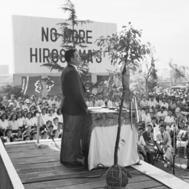 Guy at a platform speaking to a crowd with sign No More Hiroshimas