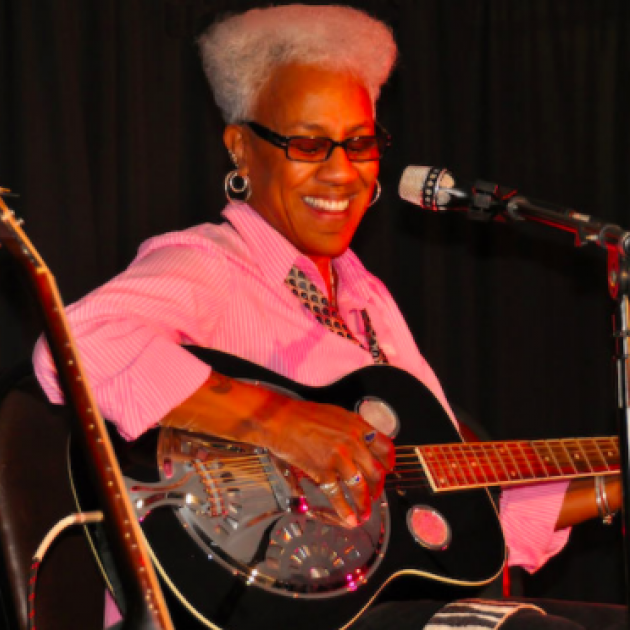 Gaye Adegbalola playing a guitar