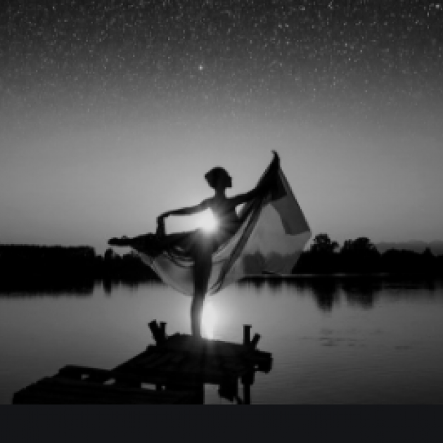 Silhouetted figure of woman posing near a lake and horizon