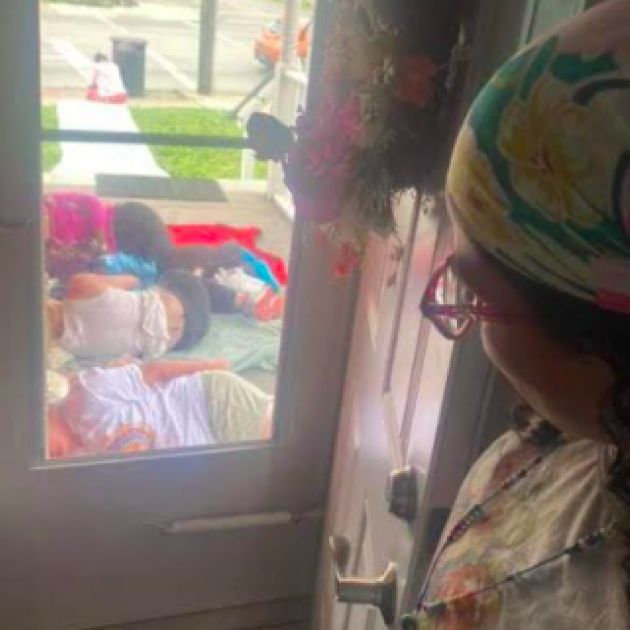 Looking out a window of women sleeping on the ground