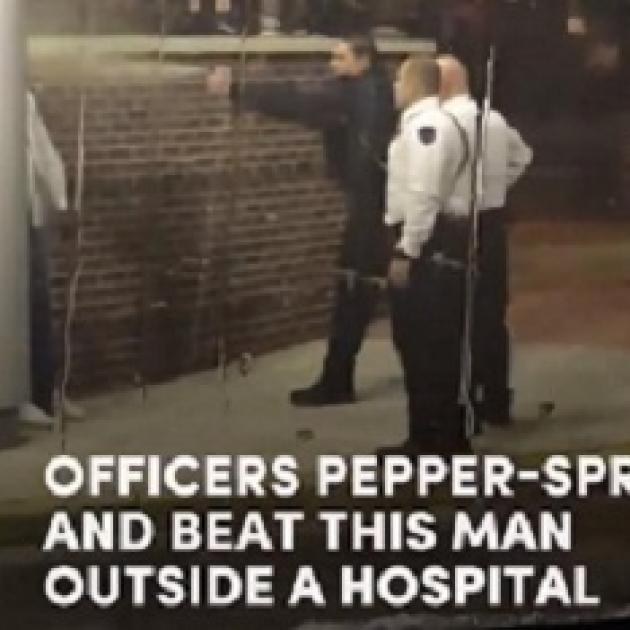 Photo of three white policemen outside one spraying pepper spray at a black man