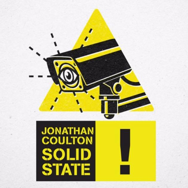 Yellow triangle with security camera with an eye on the screen above black words on yellow saying Jonathan Coulton Solid State excalamation point