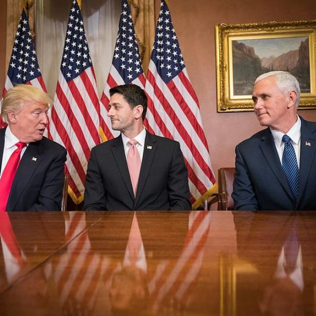 Trump, Ryan and Pence at a table looking at each other with flags in the back