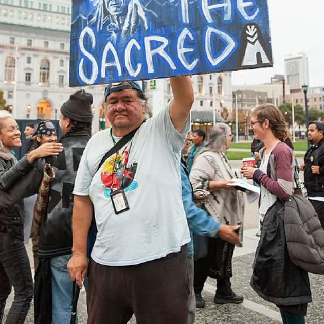 Native man holding sign about Standing Rock