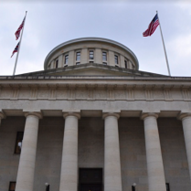 Big white government building with columns and a round top and  flags flying on each side