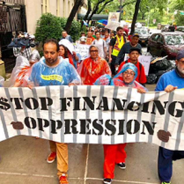 People wearing colorful clothes and raingear marching outside holding a banner reading Stop Financing Oppression