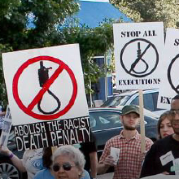 People marching with signs that say Abolish the Death Penalty and Stop Executions