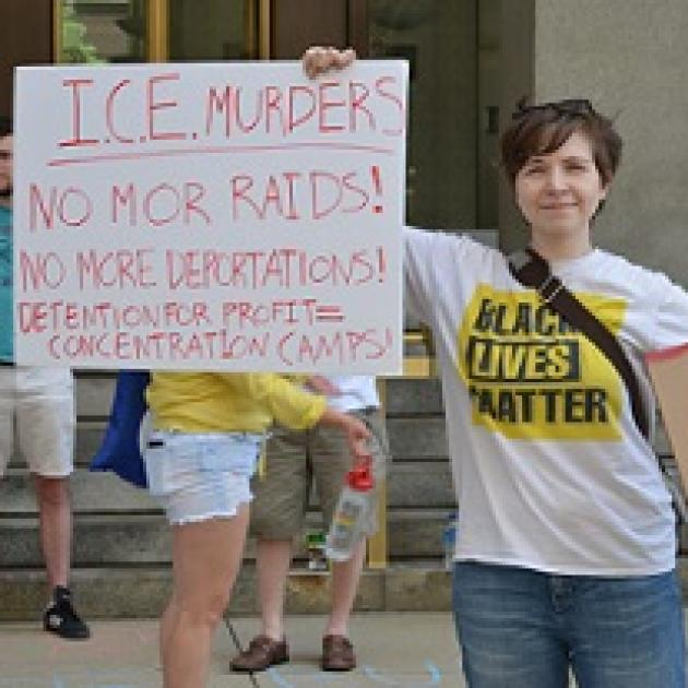 White woman in Black Lives Matter Tshirt holding a sign that says ICE murders