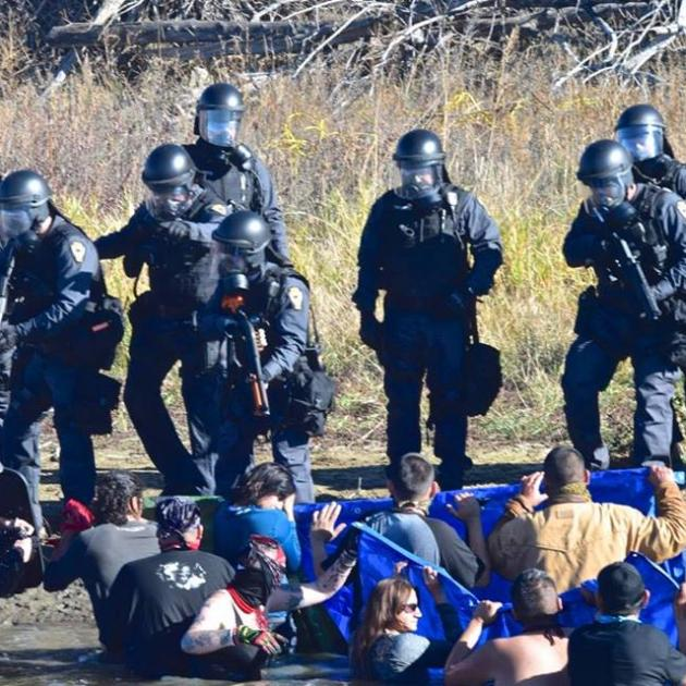 Photo of heavily armed soldier-looking men pointing guns at Native American protestors sitting on the ground