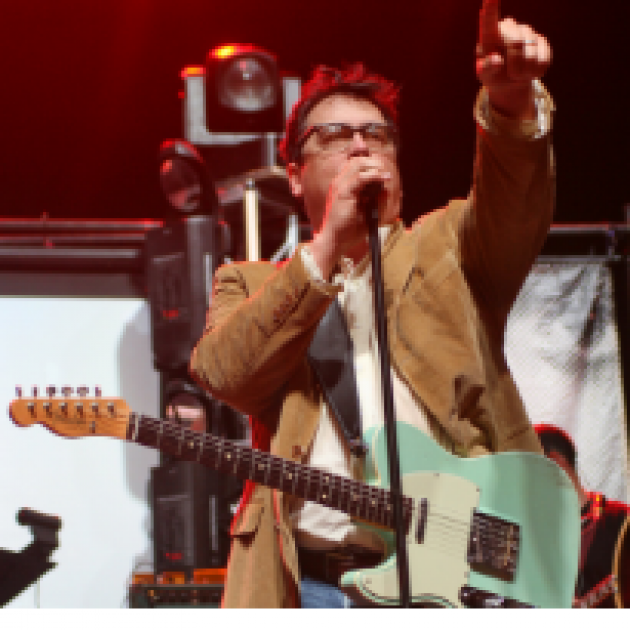 White brwon-haired man with glasses singing at a mic with a guitar around his neck and he's pointing up in the air