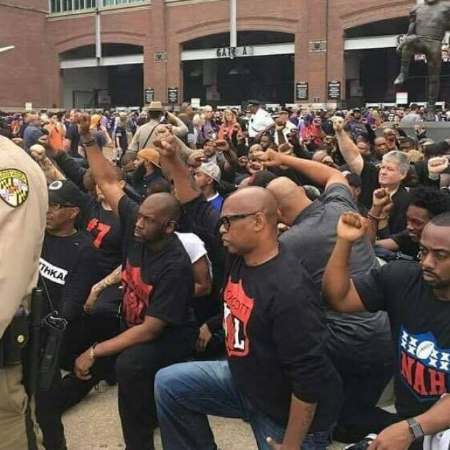 Lots of black men down on one knee with fists raised in the street with police man in foreground