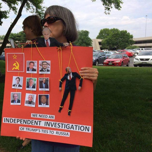 Woman standing outside with sunglasses on holding a huge red sign in front of her asking for an independent investigation of Trump's ties to Russia