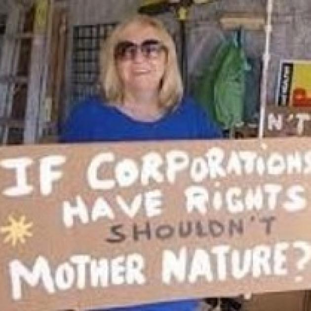 Blonde white woman with sunglasses holding a sign and smiling sign says If Corporations have rights shouldn't mother nature?