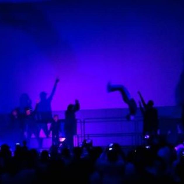 Silhouettes of people dancing and flipping in the air against a bright blue background on a stage in front of an audience