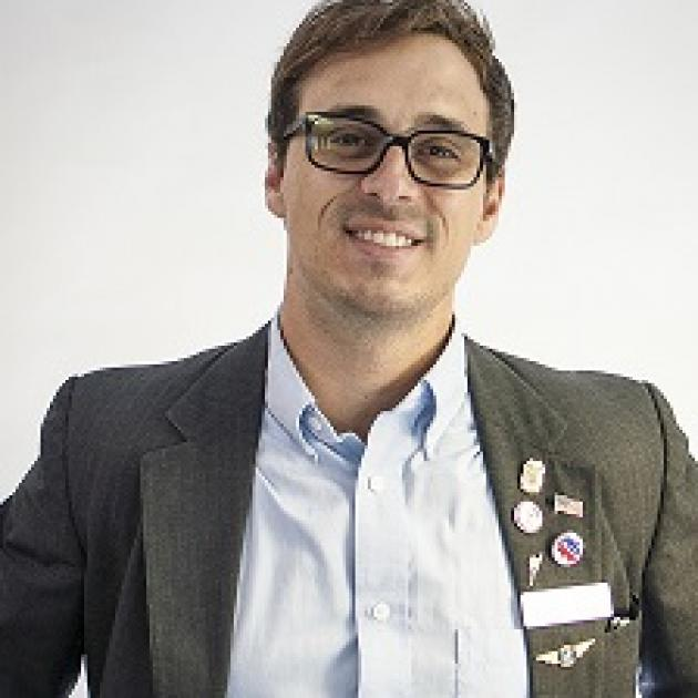Travis Irvine in a suit and glasses