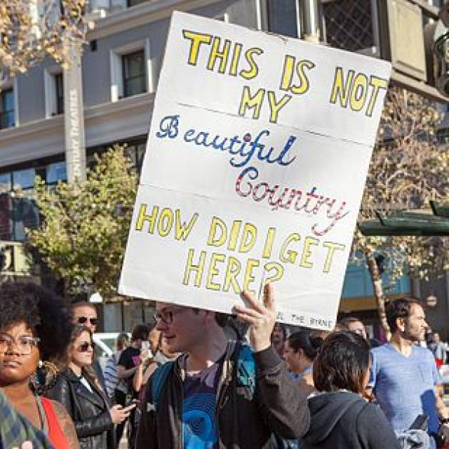 """Guy holding sign saying """"This is not my beautiful country, how did I get here?"""