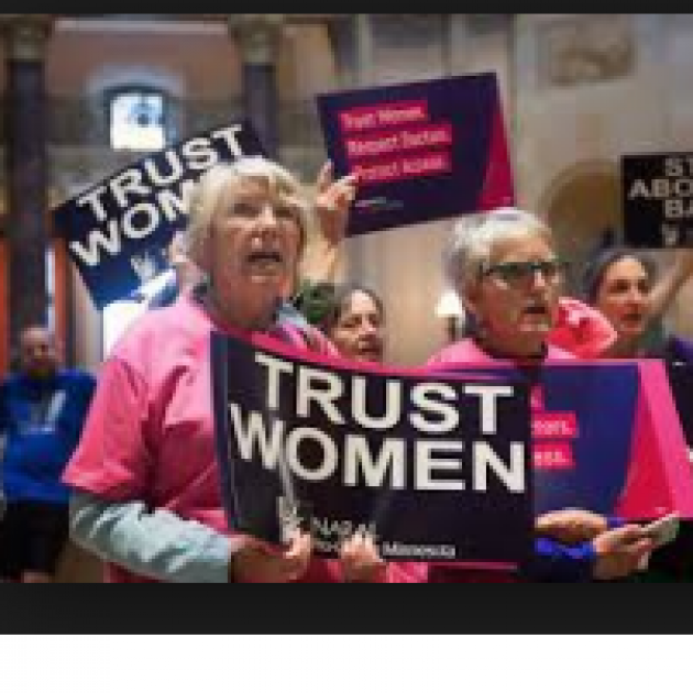 Two older women at a rally holding a sign saying Trust Women