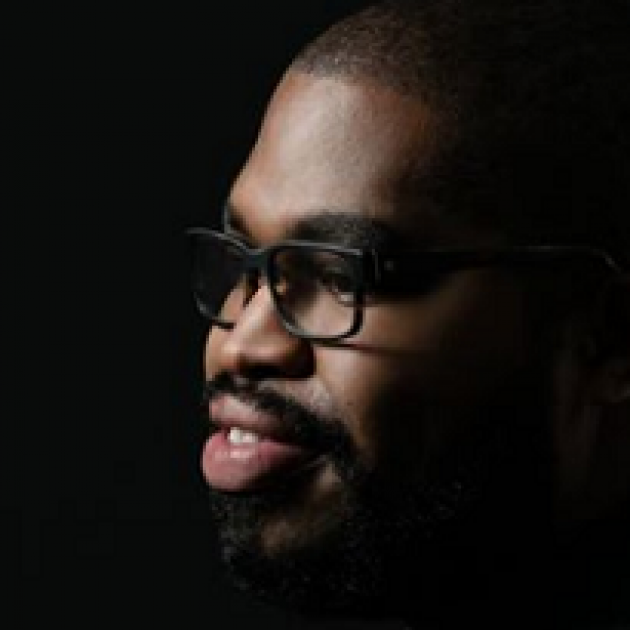 Black man's face looking left with glasses and a goatee
