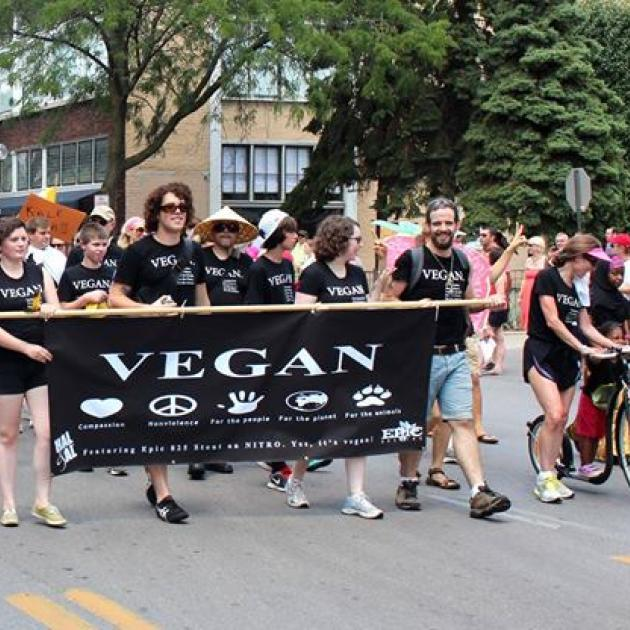 People in black and white Vegan shirts holding Vegan sign marching in parade