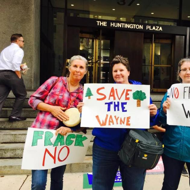 Three women holding signs about saving the Wayne National Forest