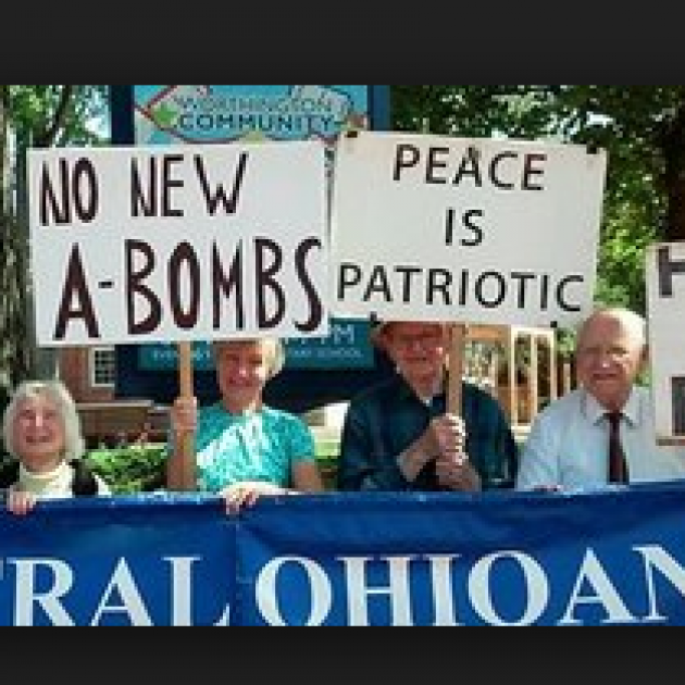 People marching outside with trees in background carrying signs, No New A-Bombs, Peace is Patriotic