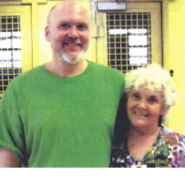 Tall bald white man with a mustache and beard and green T-shirt standing smiling with his arm around a gray haired smiling lady in a flowered dress