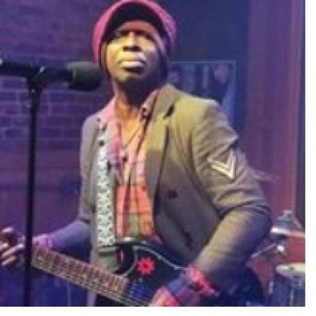 Black man in a hat playing a guitar at a mic