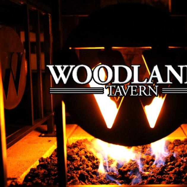 Fire in stove behind words Woodlands Tavern