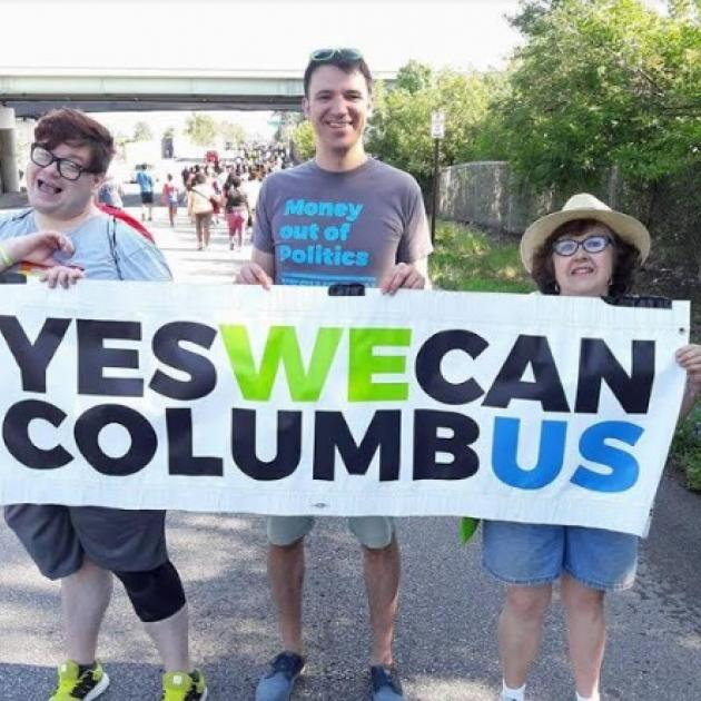 People outside holding a Yes We Can banner