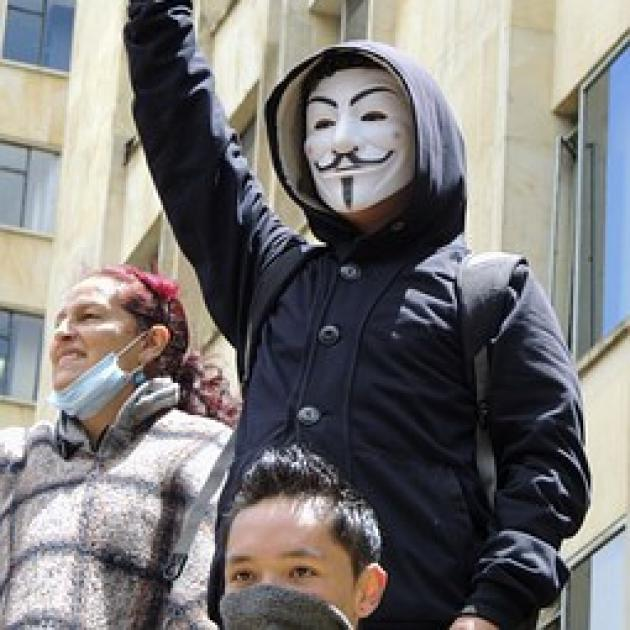 Guy wearing anonymous Guy Fawkes mask with fist in air at protest with others