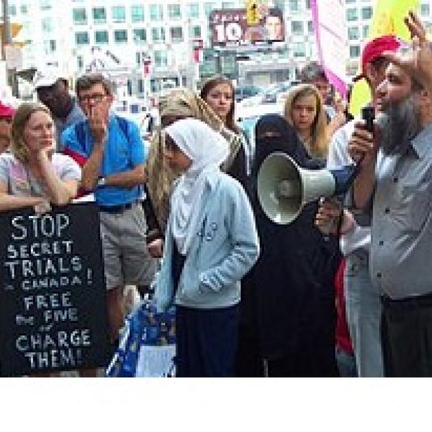 People protesting outside with sign saying Stop secret trials