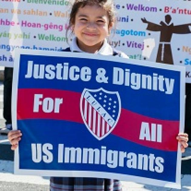 Very young Latino-looking girl holding a red white and blue sign that says Justice & Dignity for all US immigrants