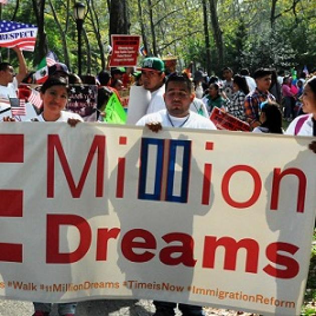 Latino young people marching and holding sign that says Million Dreams