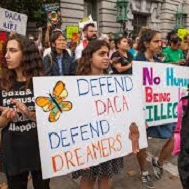 Young people holding signs outside a building that say Defend DACA Defend Dreamers