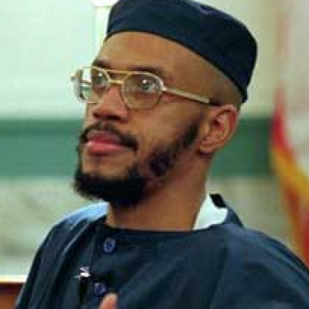 Black man  with wire-rimmed glasses and a mustache and beard