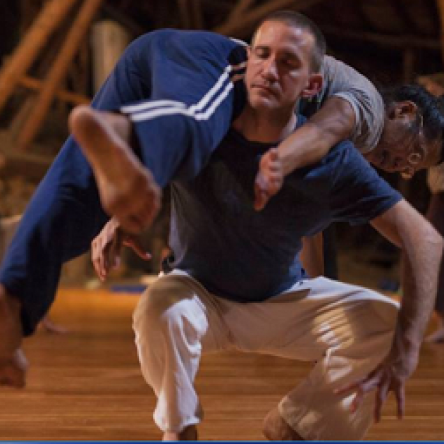 White middle aged man squatting with his eyes closed holding a woman across is back in a dance move