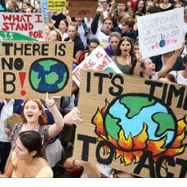 Lots of people outside from a view above all holding signs like There is no planet B and It's time to Act