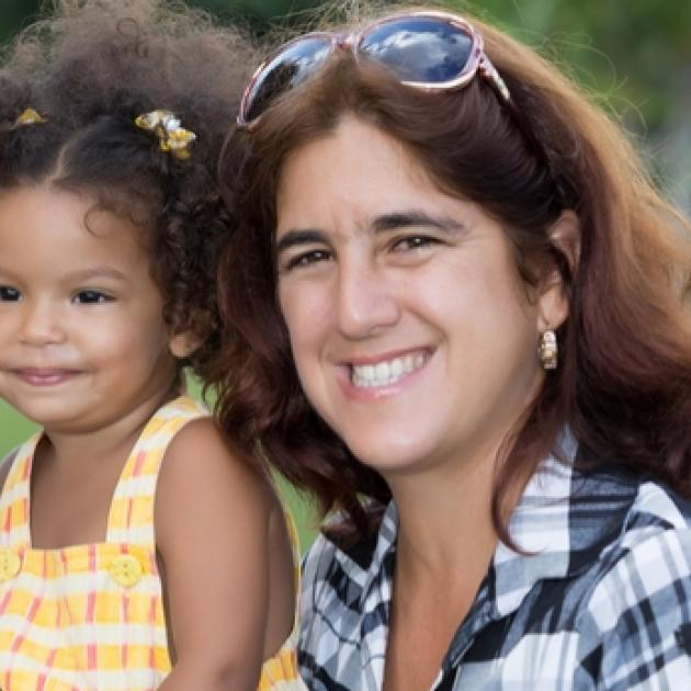 Young black girl with thirty-something white woman with brown hair and sunglasses on her head