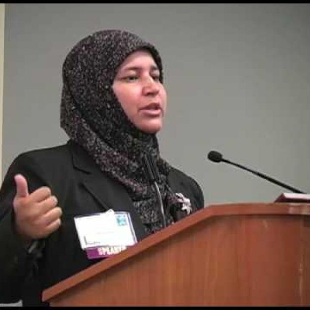 Muslim woman speaking at a mic