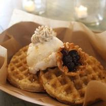 Two brown waffle-ish looking foods on a plate with a dollup of something white and something purple
