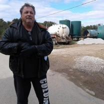 White man in winter coat standing in front of metal tanks and a truck
