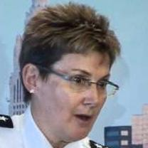 White women with glasses and short brown hair wearing a police uniform looking surprised