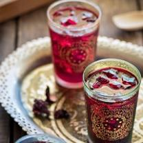 Two glasses with gold designs on the outside and red liquid inside on a pretty gold flouted tray against a wooden tabletop