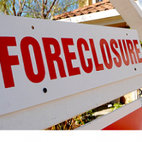 White sign with red letters saying Forclosure in front of a house