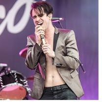 Young white man with satiny suit jacket and no shirt with shaggy brown hair singing intoa ic