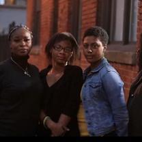 Three black women standing outside a brick building