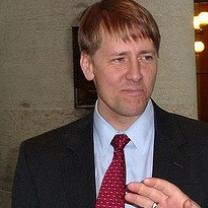 White man in a dark suit, white shirt, red tie with shaggy blonde hair with a pensive worried look